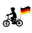 A kid rides a bicycle with German flag vector image vector image