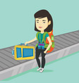 woman picking up suitcase on luggage conveyor belt vector image