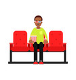 young man sitting in the cinema with popcorn and vector image vector image