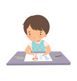 cute boy sitting at desk and drawing picture vector image vector image
