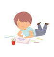 cute boy lying on his stomach and drawing picture vector image vector image