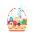 easter bunny in a wicker basket with colored eggs vector image