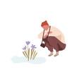 squatting man admiring first spring flower