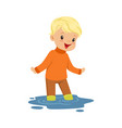 cute blonde little boy playing on a puddle wearing vector image vector image