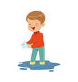 cute little boy playing with paper boat in a water vector image vector image