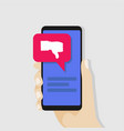 hand holding smartphone with red dislike on screen vector image vector image