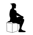 man sitting on box with one foot up on knee vector image
